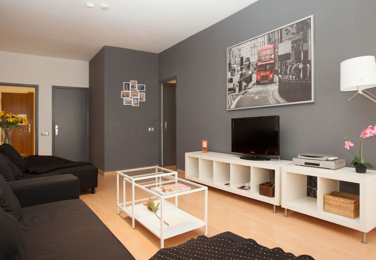 living room with TV and large couch in 4-bedroom apartment close to Plaza España Barcelona