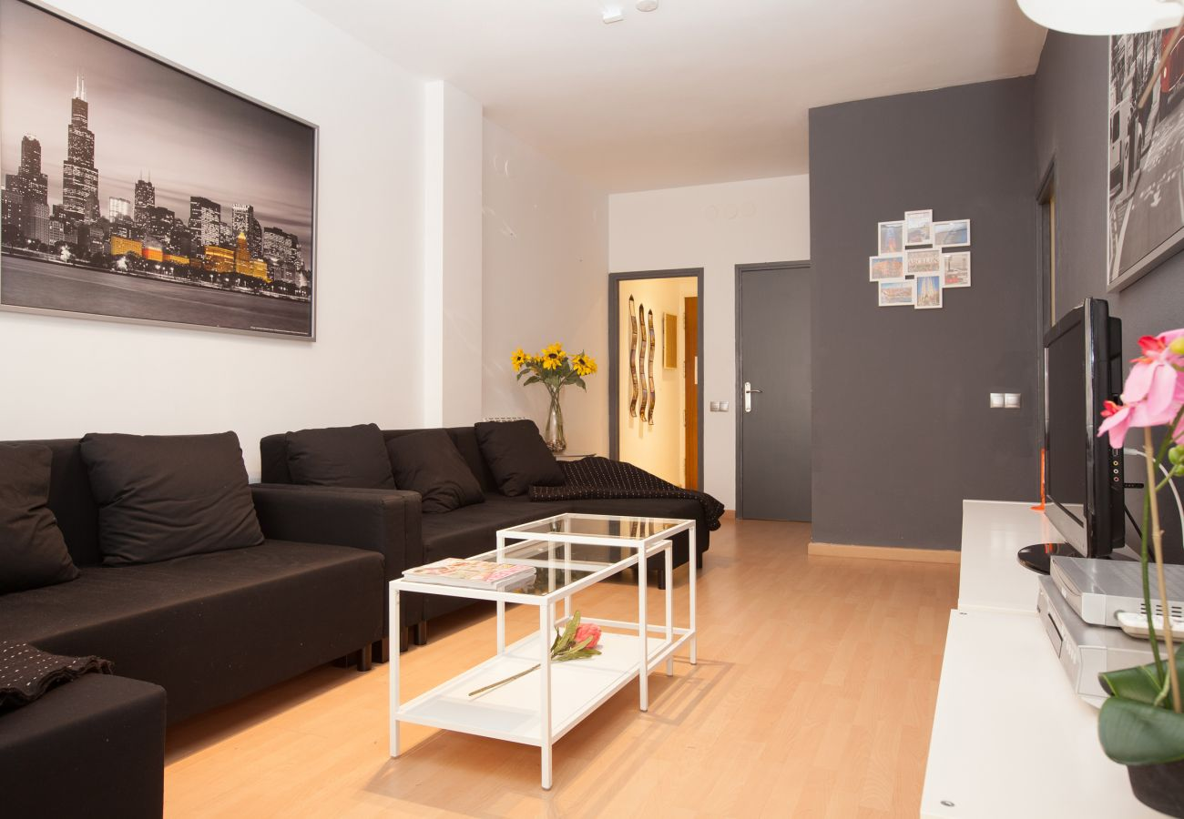 living room with large sofa and TV of 4-bedroom apartment close to Plaza España Barcelona
