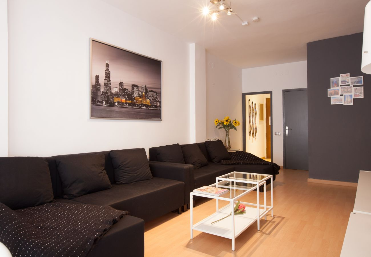 large sofa in the living room of 4-bedroom apartment close to Plaza España Barcelona