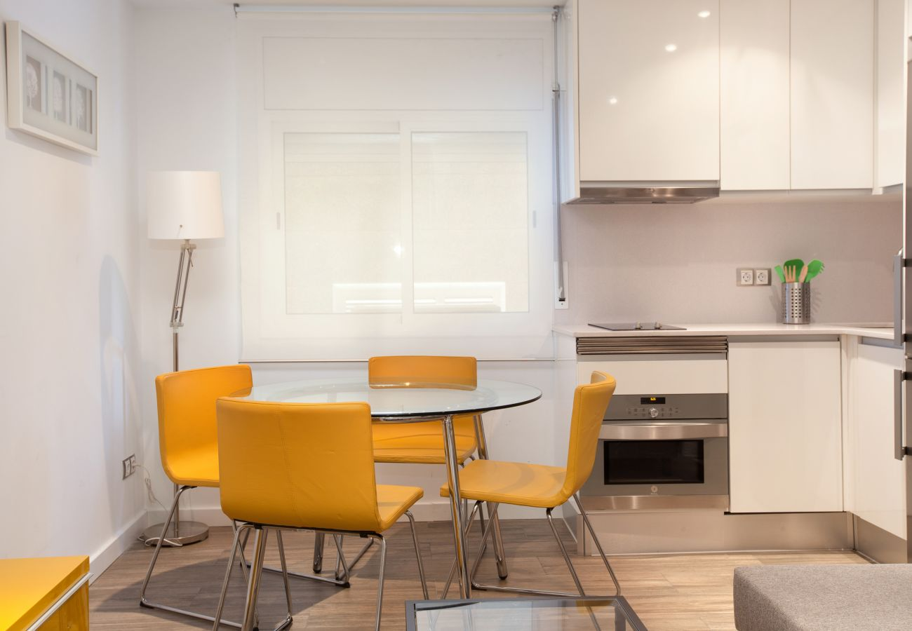 dining table with chairs and American kitchen in 2-bedroom apartment in Barcelona
